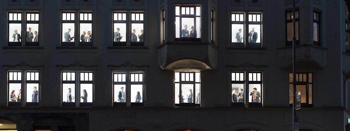 Fassade Bürogebäude mit Anwälten vor Fenstern