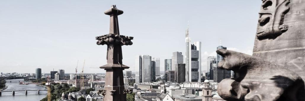 Bild einer Stadt, rechts eine Statur, links ein Fluss