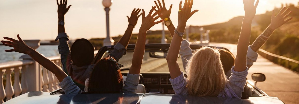 Bild von 4 jugen Leuten im Auto, welche alle die Hände in die Luft strecken