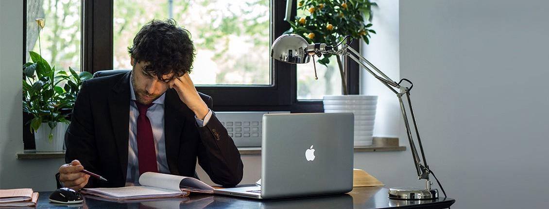 Bild Ilja Ruvinskij am Schreibtisch sitzend mit Laptop und Unterlagen