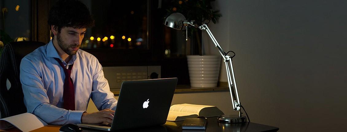 Bild von Ilja Ruvinskij spät abends am Schreibtisch sitzend mit Laptop und Unterlagen