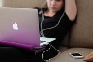 Bild von Mädchen mit Laptop und Handy mit Kopfhörern im Ohr