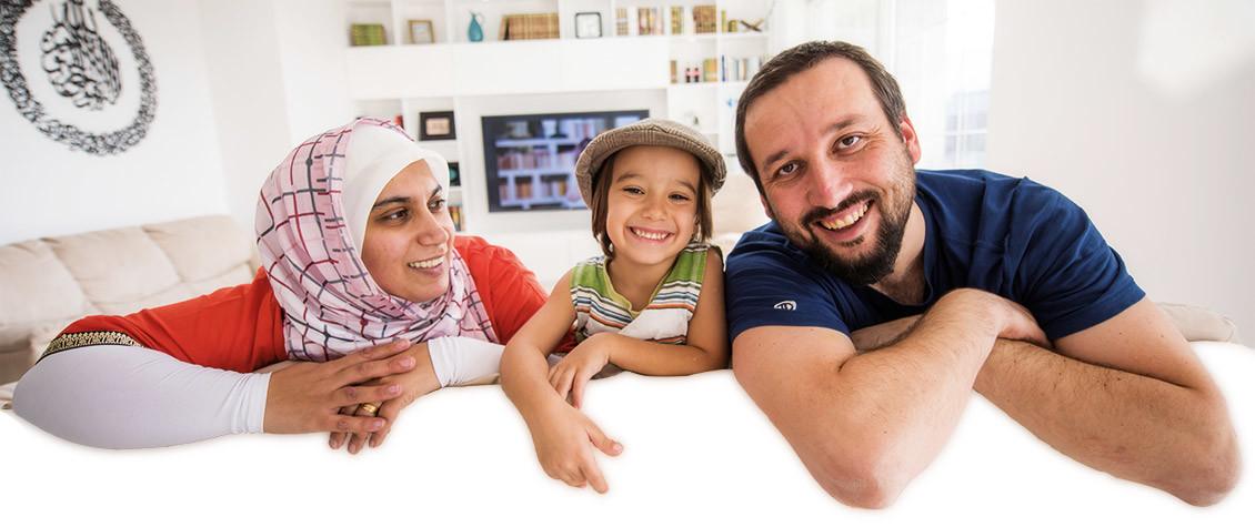 Bild von glücklichen Eltern mit Kind in der Mitte in ihrem Wohnzimmer