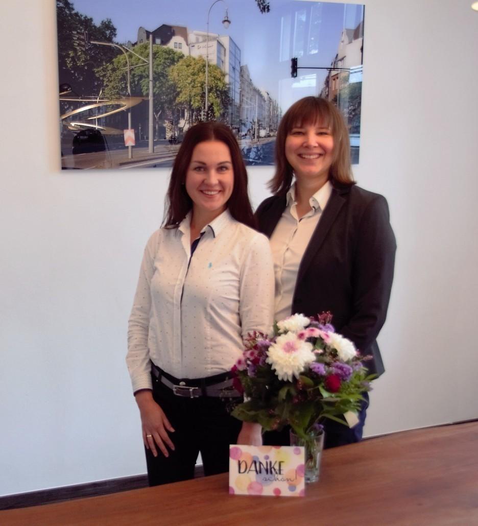 Rechtsanwältinnen mit Blumen und Dankeskarte