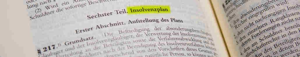 Aufgeschlagenes Gesetzbuch. Wichtiger Paragraph zum Insolvenzplan ist markiert.