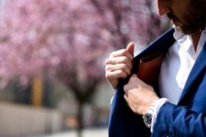 Bild von einem Mann, der seinen Geldbeutel in sein Jacket steckt.