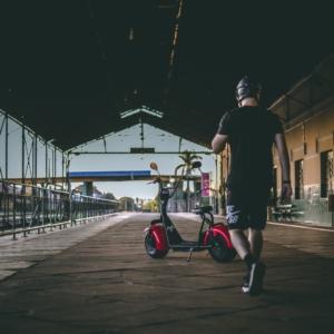 Bild eines E-Scooters und Mann mit Sturzhelm