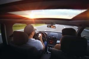 Foto des Innenraums eines Autos mit einem am Handy spielenden Fahrers mit Beifahrerin