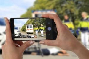 Foto von Händen, welche mit einem Handy eine Unfallstelle fotografieren