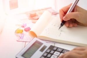 Bild von Taschenrechner und jemanden, der seine Finanzen notiert