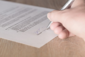 Bild von einem Vertag, welcher gerade unterschrieben wird
