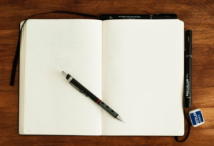 Bild von einem offen liegenden Notizheft mit Kugelschreiber