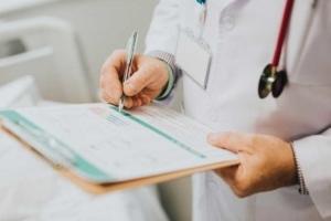 Foto von Arzt der etwas auf ein Klemmbrett schreibt