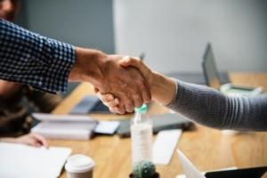 Bild von zwei Personen, welche sich in einem Büro die Hand geben