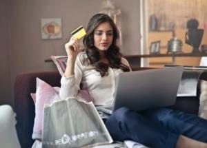 Bild von junger Frau mit Kreditkarte in der Hand, vor dem Laptop sitzend