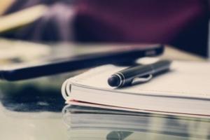 Bild von Laptob und einem Kugelschreiber auf einem Block