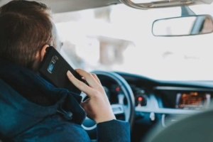 Mann am Steuer mit Telefon am Ohr