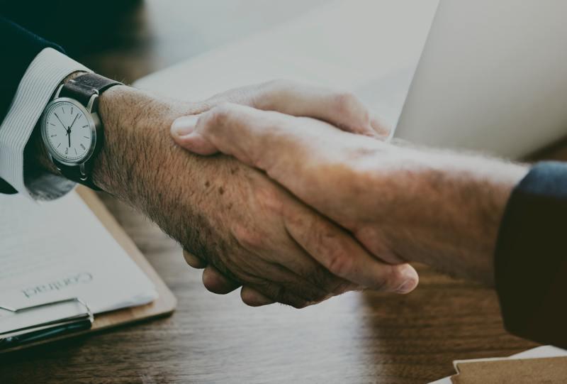 Zwei Männer reichen sich die Hand.