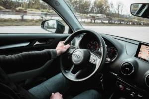 Bild von Lenkrad und Armaturenbrett eines Autos auf der Autobahn