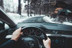 Foto während der Fahrt durch verschneiten Wald aus Sicht des Fahrers