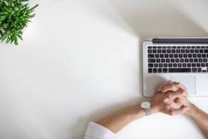 Bild von gekreuzten Männerhänden vor einem Laptop