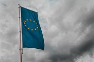 Bild von einer europäischen Flagge vor grauen Wolken
