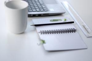 Bild von Tasse, Laptop, Notizblock und Stift mit Lineal
