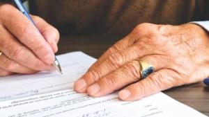 Person unterschreibt Dokumente