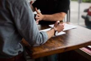 bild von zwei Männern am Tisch während einer vermutlichen Diskussion