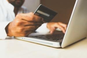 Bild von einem Mann am Laptop mit einer Kreditkarte in der Hand