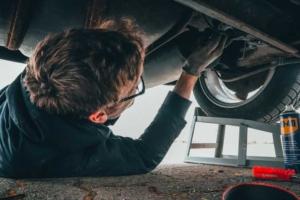 Mann untersucht Auspuffanlage eines Autos