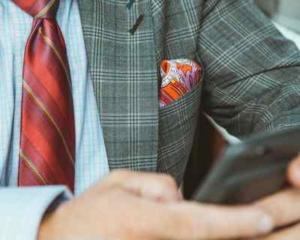 Bild von Mann im Anzug mit Krawatte und Handy in der Hand