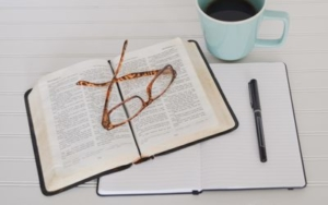 Bild von einem Buch, Notizheft, Kaffe, Stift und Lesebrille
