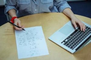Bild von einem Blatt, Händen und Laptop