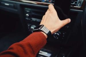 Bild von Handgelenk mit Smartwatch und Hand im Auto