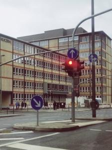 Bild von einer roten Ampel und Verkehrszeichen zur vorgegeben Fahrtrichtung
