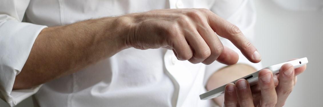 Bild von Männerarmen, Nutzung eines Handys