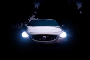 Silbergraues Auto mit eingeschalteten Scheinwerfern bei Dunkelheit