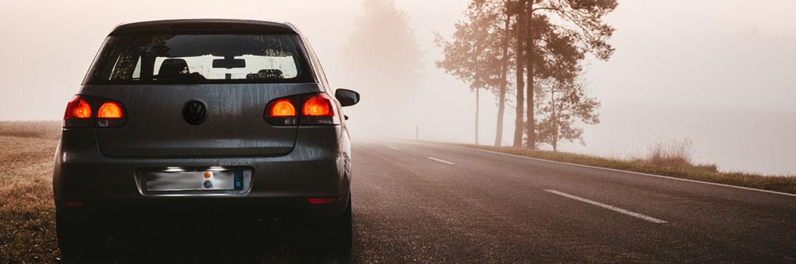 Bild von VW Golf auf verlassener Straße im Nebel