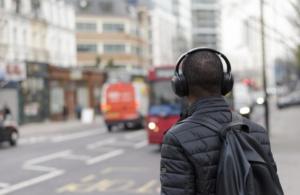 Junger Mann mit Kopfhörern auf dem Bürgersteig