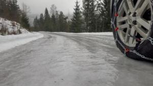Autoreifen mit Schneeketten auf eisglatter Fahrbahn