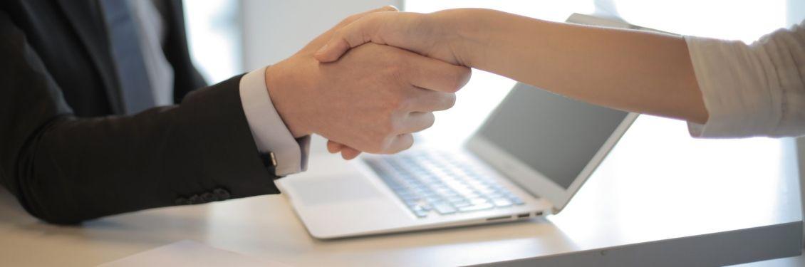 Zwei Menschen geben einander die Hand.