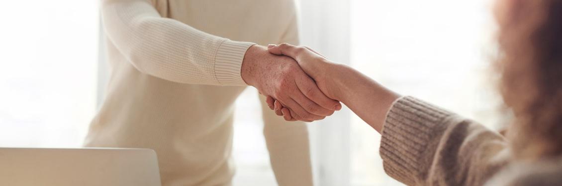 Ein Mann und ein Frau schütteln sich die Hände.