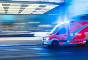 Krankenwagen rast mit Blaulicht die Straße entlang
