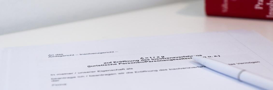 Das Bild zeigt einen Taschenrechner und zwei Bücher aus dem Insolvenzrecht