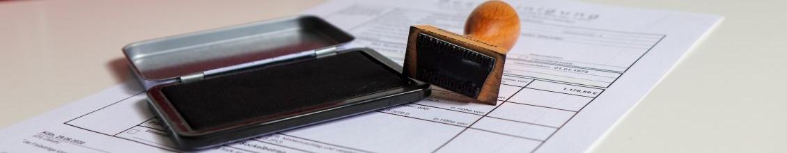 Das Bild zeigt ein Dokument und einen Stempel
