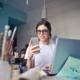 Bild von einer Frau mit Handy und Laptop