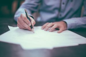 Mann unterschreibt Unterlagen