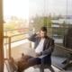 Bild von einem konzentrierten Mann mit Laptop auf Balkon