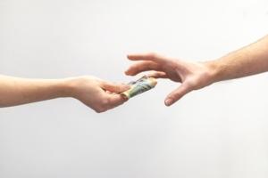 Bild von zwei Händen und Geldscheinen